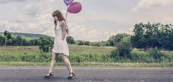色とりどりの風船を持ちながら歩く女性