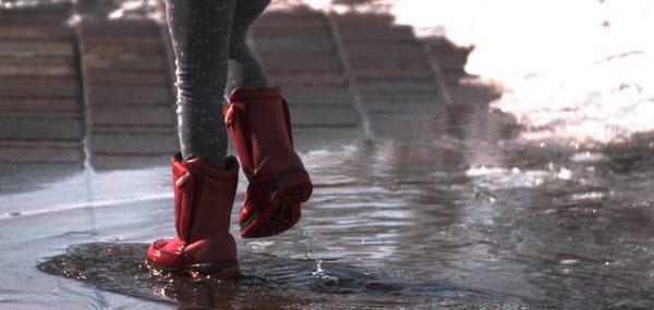 水たまりを楽しそうに歩く綺麗な足の女性