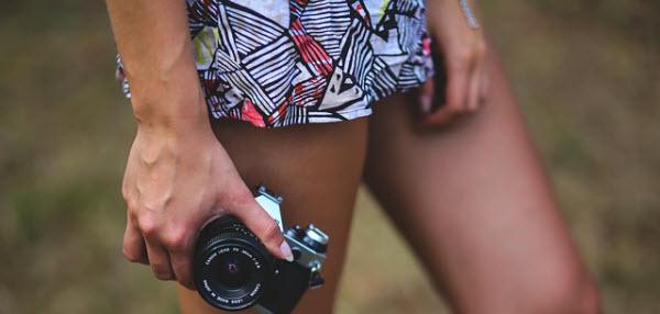 カメラを片手に持つ脚線美の女性