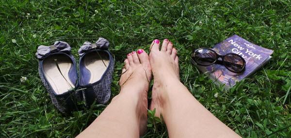 芝生で休憩する素足の綺麗な女性