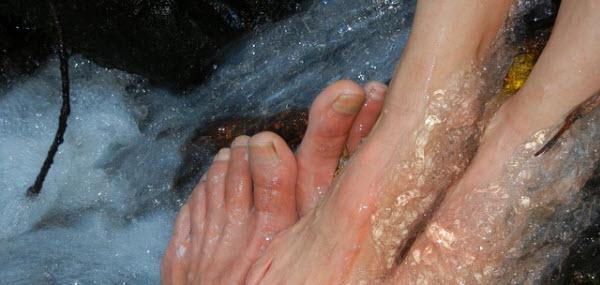 恋人と自慢の足を川に入れる女性