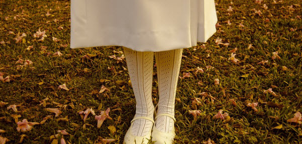 紅葉の森に佇む白いスカートの女性
