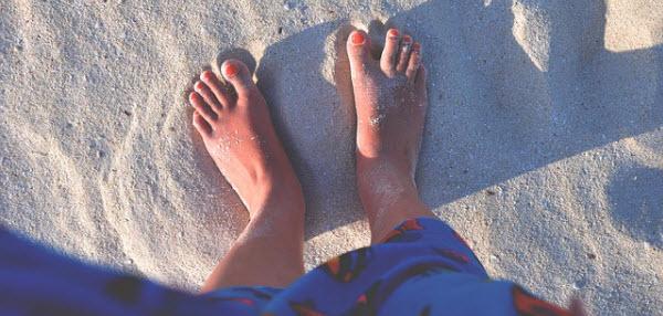砂浜で自分の脚を眺める女性