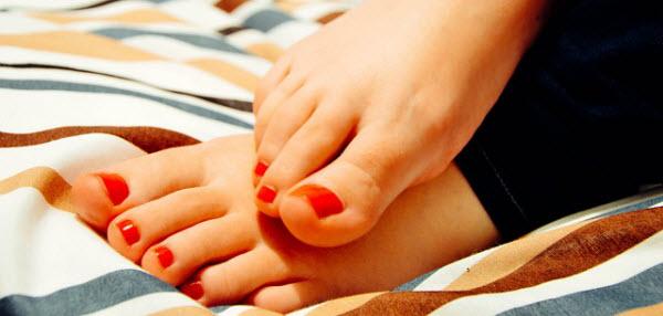 足に赤いマニュキュアを塗った女性