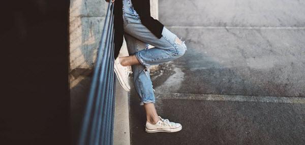 壁に持たれかかるジーンズの女性