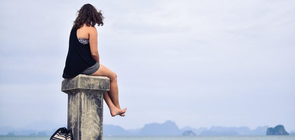 素足で海を眺める女性