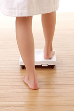 ダイエット計に乗る女性